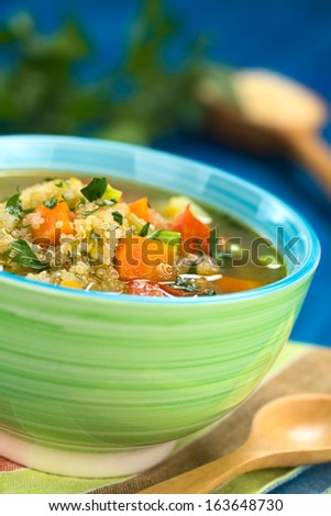 Vegetarian quinoa soup with carrot, potato, leek and tomato, sprinkled with parsley and scallion in colorful bowl (Selective Focus, Focus one third into the soup) - stock photo
