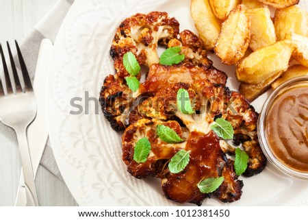 Vegetarian roasted cauliflower steak with herbs served with fried potatoes. Top view