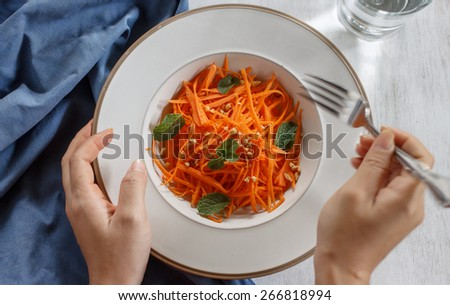 Vegetarian salad made from grated carrots and peanut with hand moving, healthy food project, good food for life - stock photo