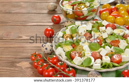 Vegetarian salad with cherry tomatoes, eggs and cheese on brown background