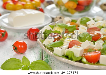 Vegetarian salad with cherry tomatoes, eggs and cheese on white background - stock photo