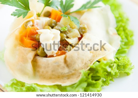 Vegetarian Salad with cooked vegetables and mayo wrapped in a pancakes on a lettuce closeup - stock photo