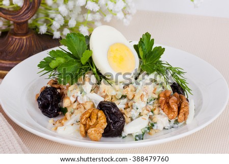 vegetarian salad with prunes and walnuts in a still life - stock photo