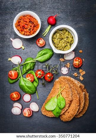 Vegetarian sandwich ingredients on dark background, top view - stock photo
