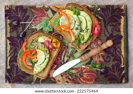 Vegetarian sandwich with avocado, bell pepper and capers - stock photo