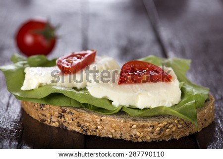 Vegetarian sandwich with cheese and vegetables on woodboard - stock photo