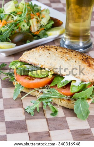 vegetarian sandwich with tomato, avocado and fresh arugula served on a wooden tay