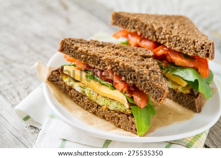 Vegetarian sandwich with zucchini burger, cheese, ruccola and tomatoes, white plate, rustic wood background, closeup