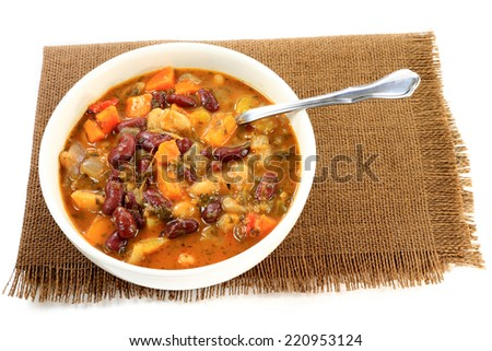 Vegetarian Soup cooked from Red and White Kidney Beans, ingredients: Carrots, Parsnips, Onion, Peppers, seasoning: Parsley, Mint, in white porcelain bowl over brown placemat on white background - stock photo