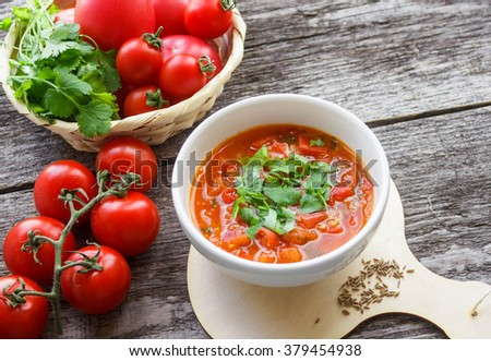 Vegetarian soup. Spicy tomato soup with herbs and spices - pepper, cumin and cilantro - stock photo