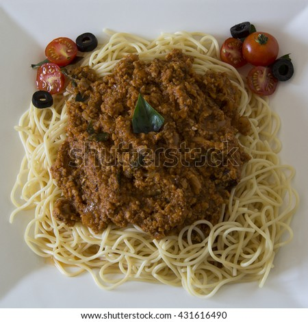 Vegetarian Spaghetti Bolognaise with minced soy (garnished with cherry tomatoes, black olives and basil leaves) - stock photo