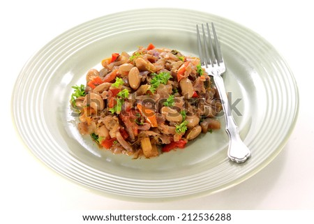 Vegetarian stew from fresh organic cabbage, vegetables - Carrot, Celery, Bell Peppers Red and Green, Tomato, White Beans seasoned with garlic, onion chopped parsley, celery leaves in dish over white  - stock photo