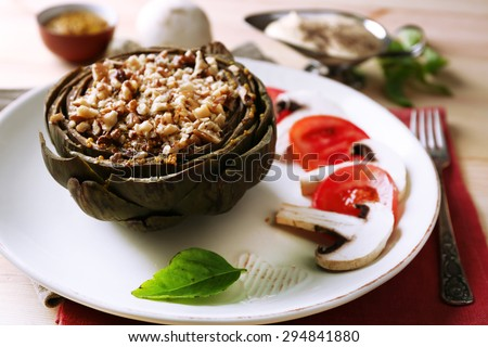Vegetarian stuffed artichoke on plate, on table background - stock photo