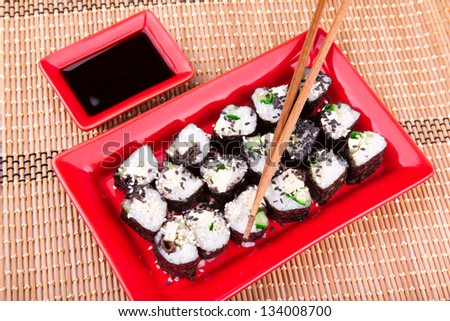 Vegetarian sushi roll served on a red plate on a bamboo mat - stock photo