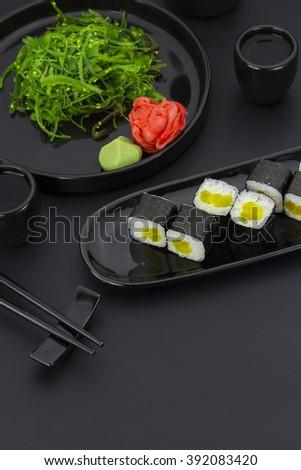 Vegetarian sushi roll with daikon ginger wasabi and chuka salad over black background - stock photo