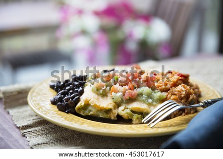 Vegetarian tamale dinner with black beans and rice topped with pico de gallo and salsa verde.