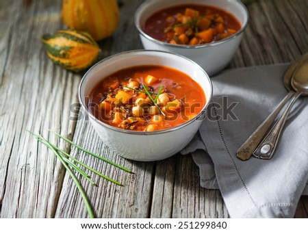 Vegetarian tasty spicy chili chick pea pumpkin wild rice soup pozole stew bowl on a wooden background  - stock photo