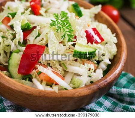 Vegetarian vegetable salad (cabbage, tomato, paprika, cucumber, onion) in a wooden bowl - stock photo