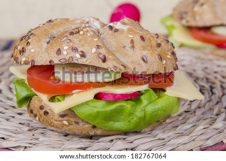 ... roll with lettuce, cheese, tomato, radish and cucumber. - stock photo