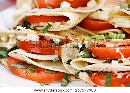 Vegetarian wraps made with goat cheese or feta, tomatoes, mozzarella and fresh herbs, Extreme shallow depth of field. - stock photo
