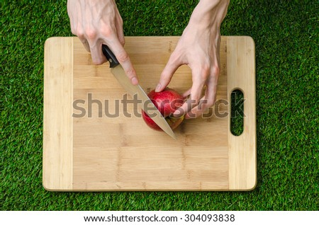 Vegetarians and cooking on the nature of the theme: human hand holding a knife and a red apple on the background of a cutting board and green grass top view - stock photo