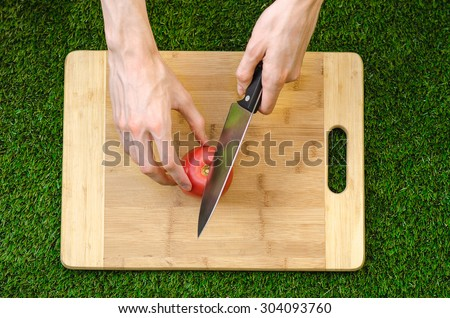 Vegetarians and cooking on the nature of the theme: human hand holding a knife and tomato cutting board on a background of green grass and top view - stock photo