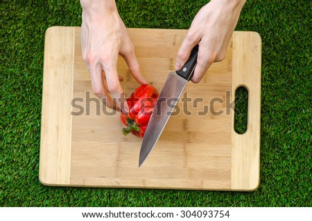 Vegetarians and cooking on the nature of the theme: human hand holding a red pepper and a knife on a cutting board and a background of green grass top view - stock photo