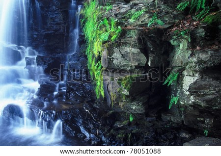 Vegetation grows along a dark cliff of Powerhouse Falls in northern Michigan - stock photo