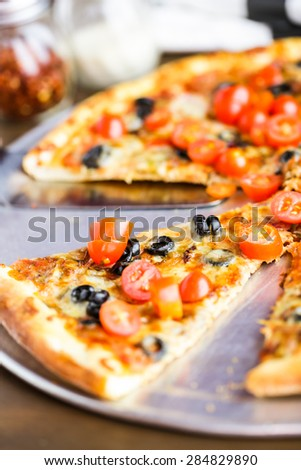 Veggie pizza with olives and cherry tomatoes on the table.