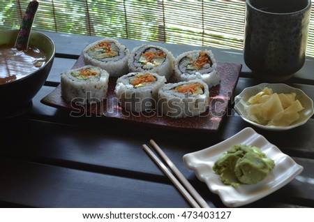 veggie sushi roll with carrot, cucumber, avacado on sushi plate, small plates ginger slices and green wasabi paste, wood chopsticks, red miso soup on black table illuminated through matchstick blind