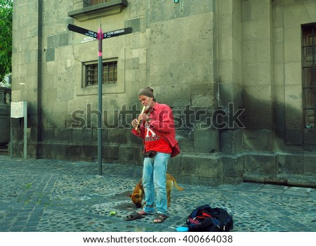 VEGUETA, GRAND CANARY ISLAND, SPAIN-MAY 11:  An unidentified busker with his dog plays a recorder for tips in historic Vegueta in Grand Canary Island, Spain on May 11, 2015. - stock photo
