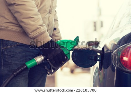 vehicle and fuel concept - close up of male refilling car fuel tank - stock photo