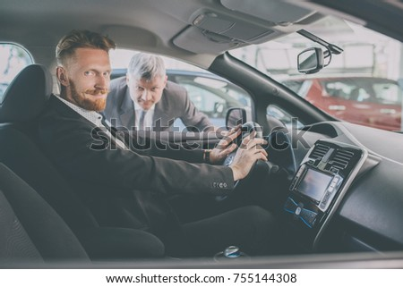 Vehicle dealer showing new car to a handsome man. Auto salon, red haired man choosing a car.