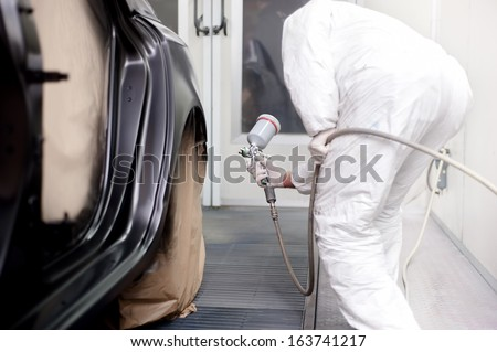 Vehicle engineer working and spraying black paint on a car in auto body shop