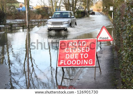 Vehicle ignoring road closed because of flooding sign. - stock photo