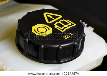Vehicle maintenance fragment, Brake and clutch fluid check cap with black cap and yellow warning information. - stock photo