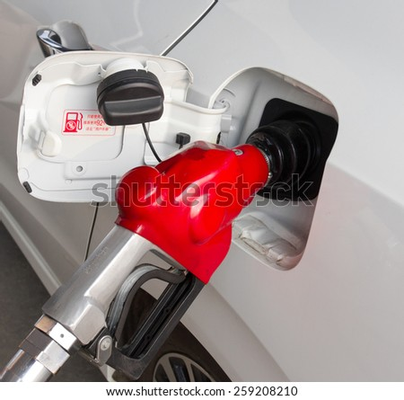 Vehicle refueling at city gas station - stock photo