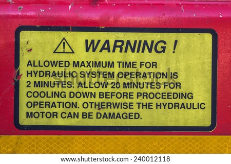 Vehicle safety reminder label on vehicle with hydraulic system - stock photo
