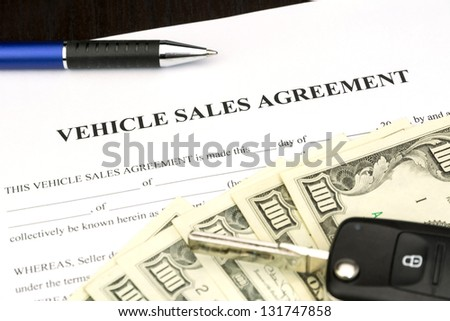 Vehicle sales agreement document contract with car key and pen - stock photo