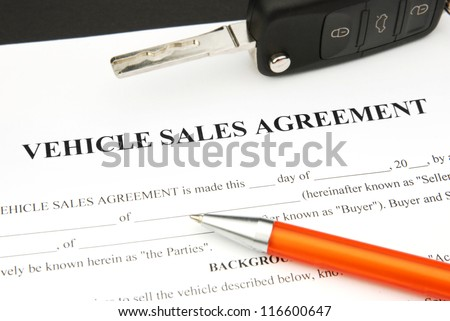 Vehicle Sales Agreement Document Form with orange Pen and Car Key