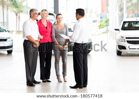 vehicle salesman explaining contract to family before purchasing a car - stock photo