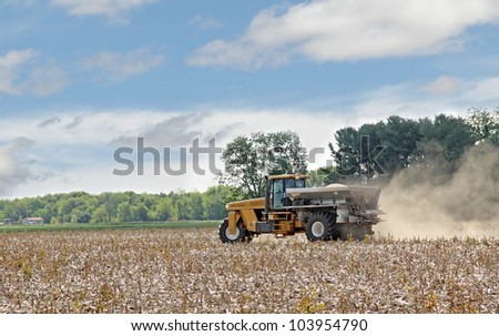 Vehicle spreading lime onto a farm field - stock photo