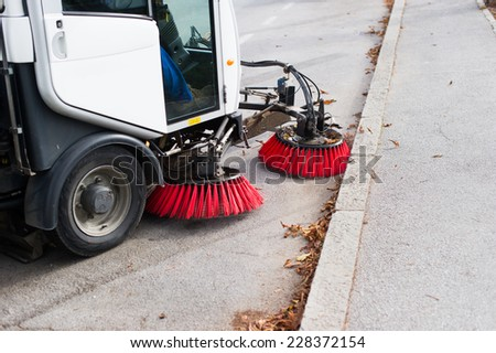 Vehicle sweeping the streets of dirt. - stock photo