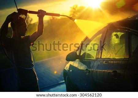 Vehicle Washing at Sunset, Hot Summer Afternoon Car Washing. High Pressure Water Washing. - stock photo