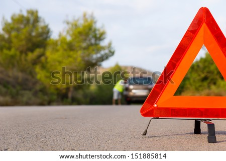 Vehicle with problems and a warning triangle - stock photo