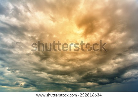 Veil of thunderclouds with warm area in center - stock photo