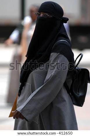 Veiled woman walking - stock photo