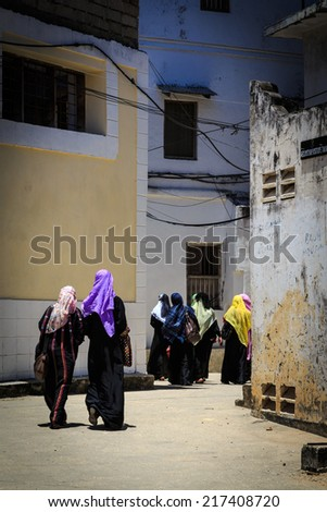 Veiled women walking through a city street at Zanzibar - stock photo