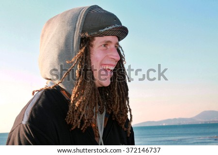 VELIKA PLAZA, MONTENEGRO JANUARY 18: Unidentified young man hippy with dreadlocks laughs on the Adriatic sea beach on January 18, 2016 in Montenegro, Velika Plaza.