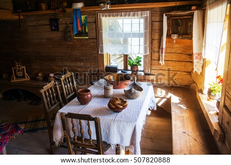 VELIKY NOVGOROD, RUSSIA - AUGUST 10, 2015: Inside a typical wooden house - table with chairs and two sun lighted windows. Museum of wooden architecture called Vitoslavlitsy
